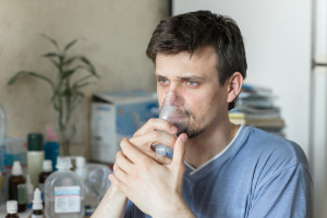 Portrait Of Young Man Inhaling Through Inhaler Mask