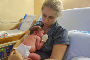 portrait of mother and newborn baby resting after childbirth in hospital room