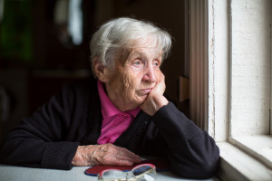 An elderly woman sadly looking out the window. Melancholy and de