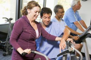Nurse With Patient In Rehabilitation Using Exercise Machine