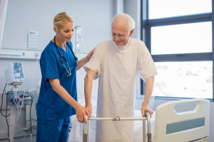Nurse helping disabled man using walker in rehab center. Happy f